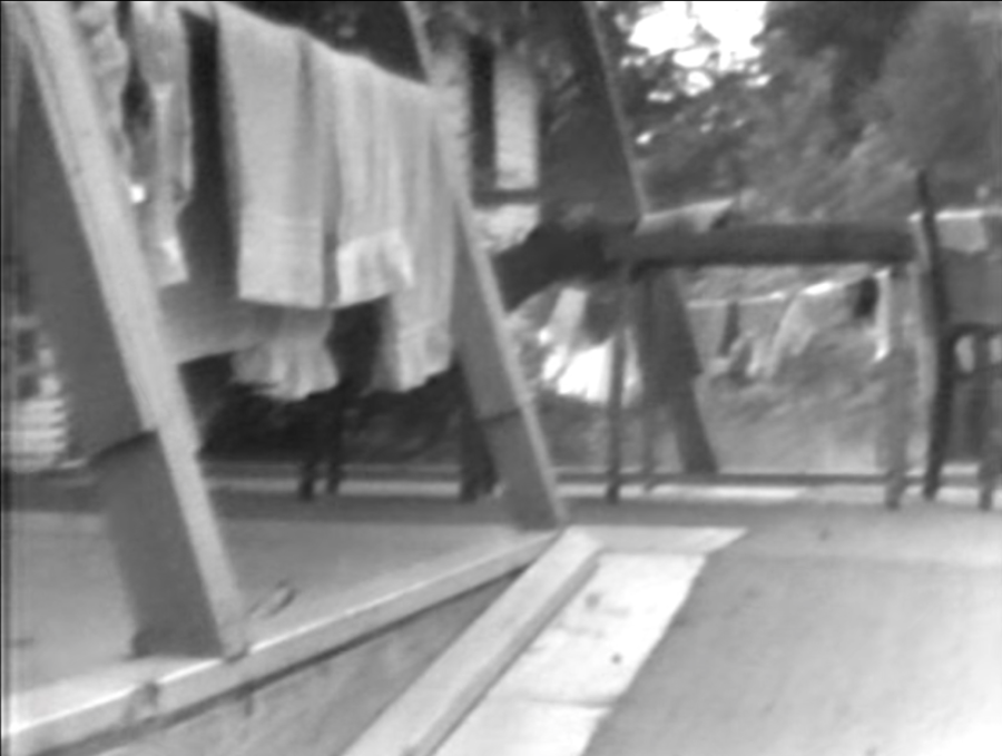 A shot from archival footage in which LeBrecht and the camera move up a ramp to the girls' dorm.