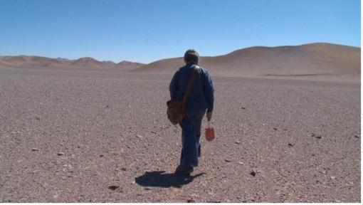 adult man walking across the Atacama desert