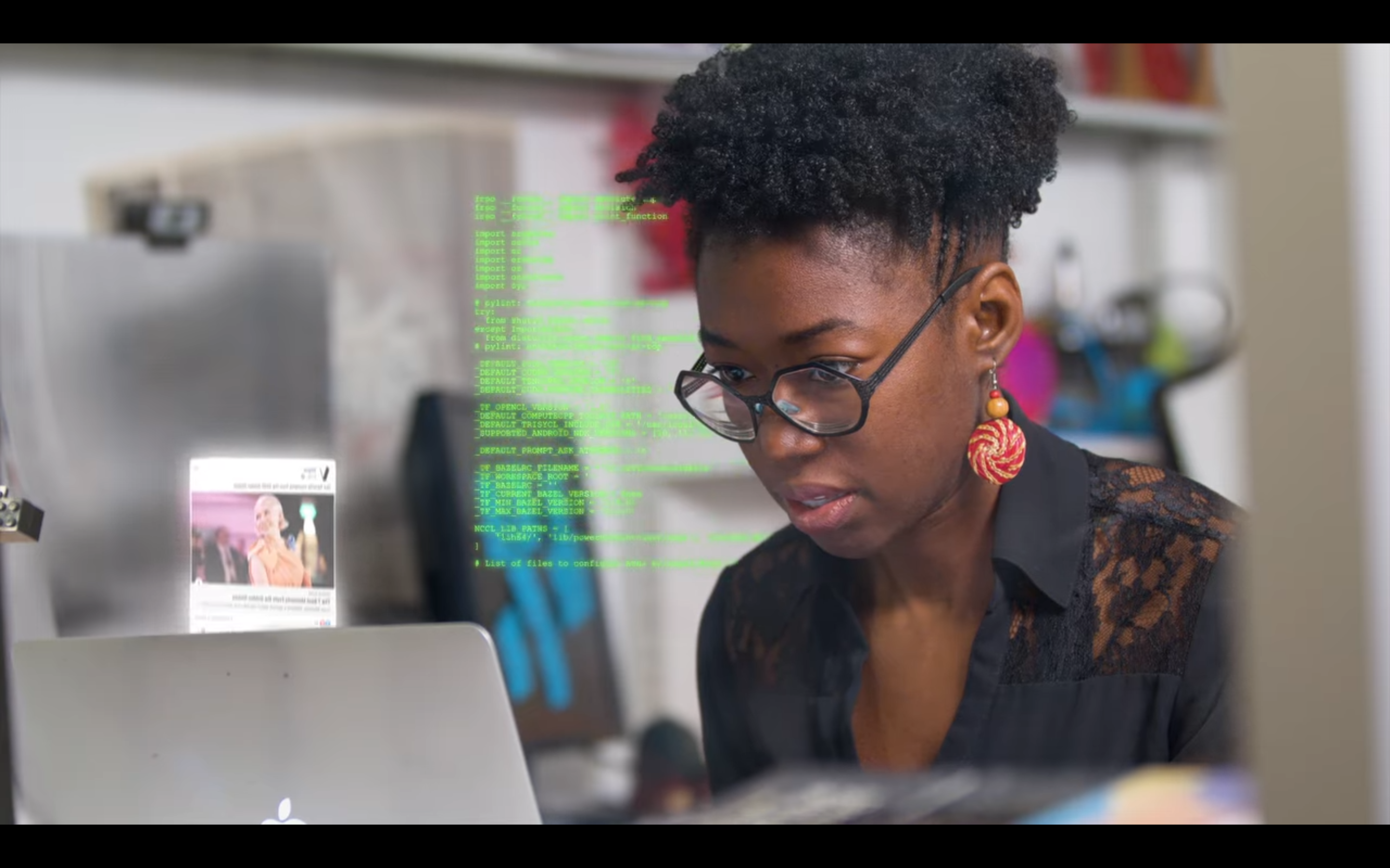 A Black woman typing at a laptop surrounding by animated data visualizations
